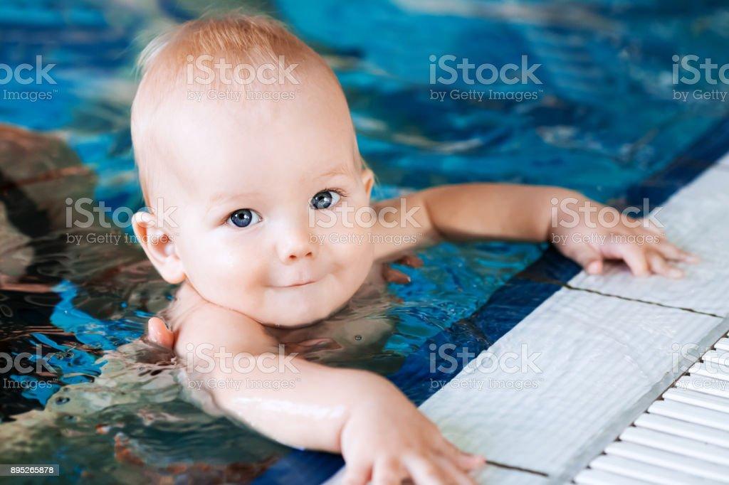 Madre de bebé de enseñar a nadar en una piscina. - foto de stock