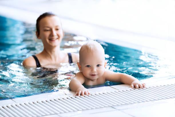 mãe de bebê de ensinar a nadar em uma piscina. - comodidades para lazer - fotografias e filmes do acervo
