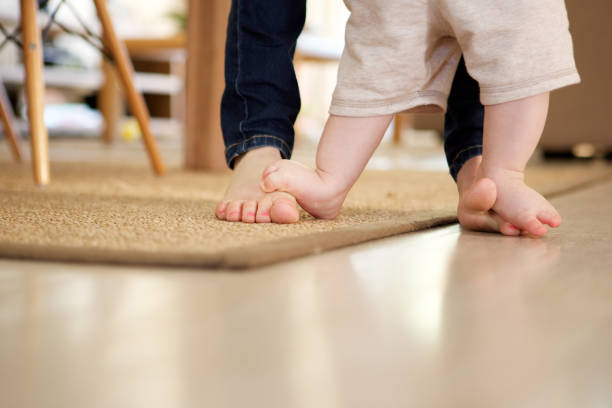 mother teaching baby to walk indoors - first step stock photos and pictures