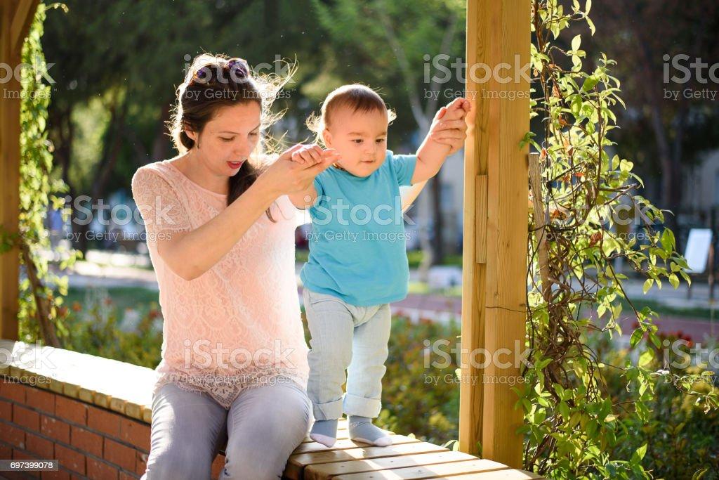 Mother teaching baby to walk stock photo