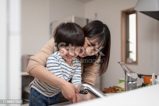 Mother teaches child how to wash hands in kitchen