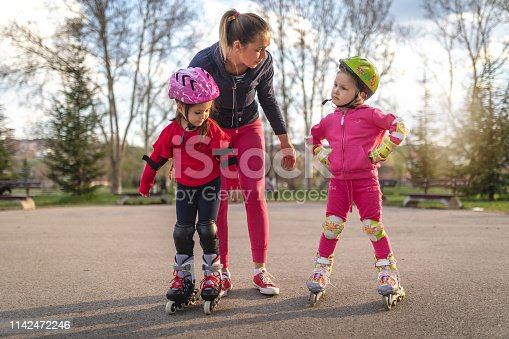 Beautiful young siblings having fun at a park with their mother, riding rollerblades.