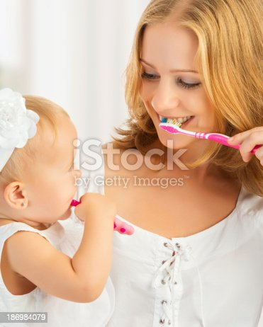 istock Mother teaching daughter how to brush teeth 186984079