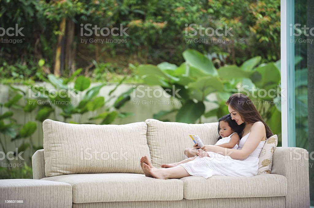 Mother Teaching Daughter how to read royalty-free stock photo