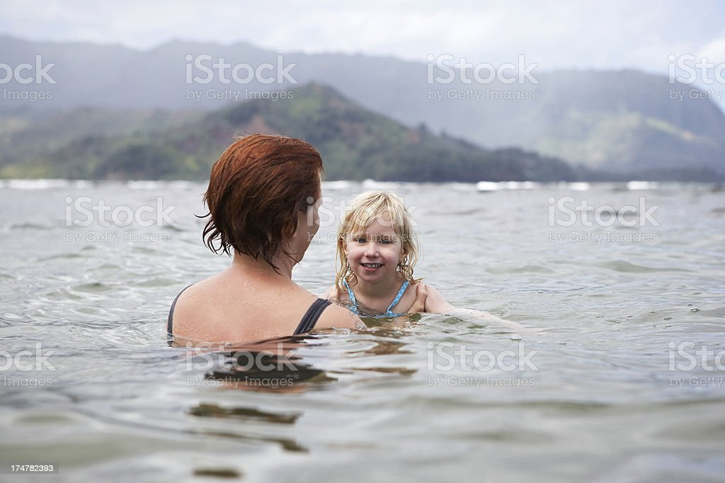 Mother teaching daughter how to swim royalty-free stock photo