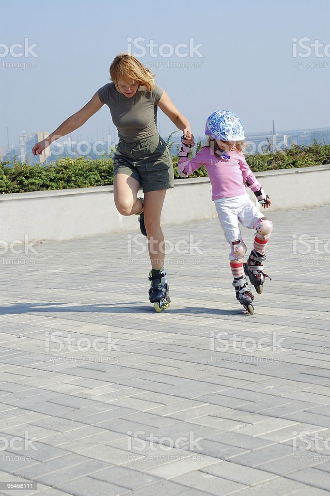 mother teaching daughter rollerblading royalty-free stock photo