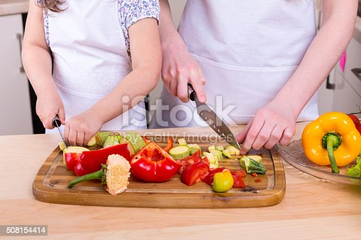 488109116istockphoto mother teaching daughter to cut vegetables 508154414