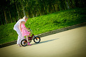 Mother teaching daughter to ride bike