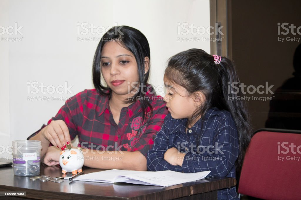 Mother with her daughter inserting coin into piggy bank while...