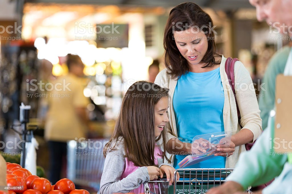 Mother teaching daughter to shop with coupons in grocery store stock photo