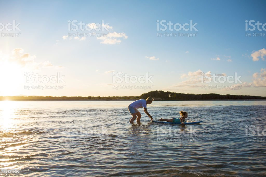 Mother teaching daughter to surf stock photo
