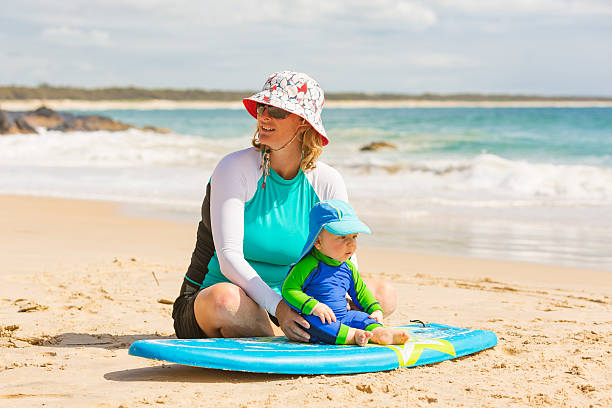 Mother Teaching Her Baby Boy to Surf Sun safe mother at the beach in Australia teaching her baby boy how to surf long sleeved stock pictures, royalty-free photos & images