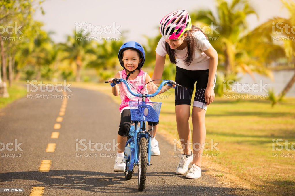 Mother teaching her daughter cycling stock photo