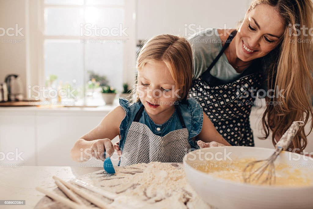 Mother teaching her daughter to cook in kitchen stock photo