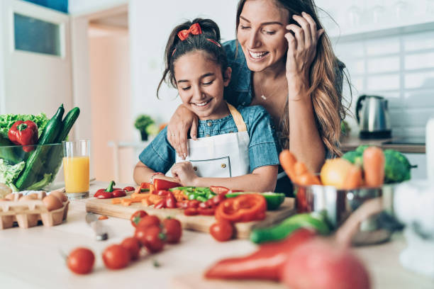 Mother teaching her daughter to cook stock photo