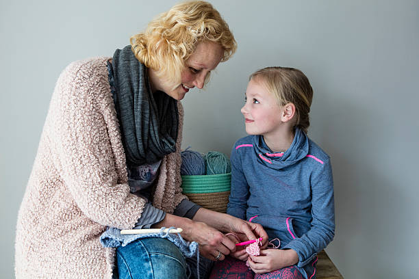 Mother Teaching Her Daughter To Crochet stock photo