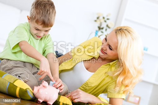 481974106istockphoto Mother teaching her little child to save money 186850834