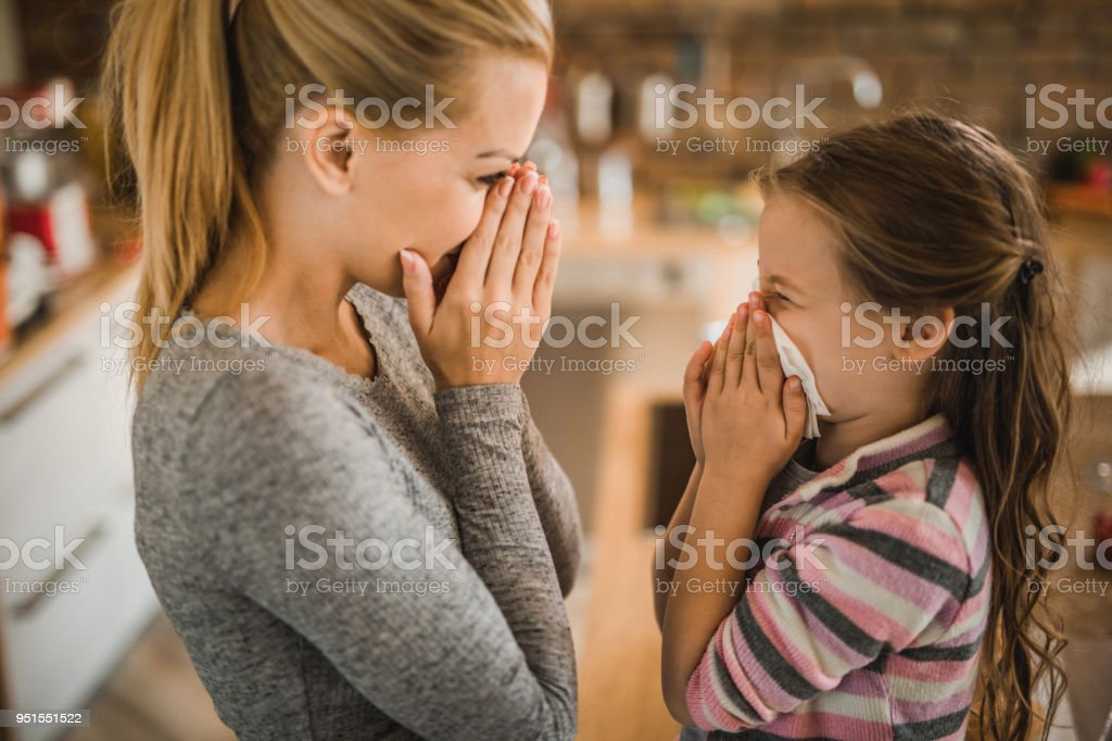Mother teaching her small daughter how to blow nose at home. stock photo