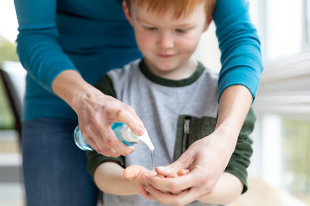 Mother teaching her son about cleaning and disinfecting hands with hand sanitizer stock photo