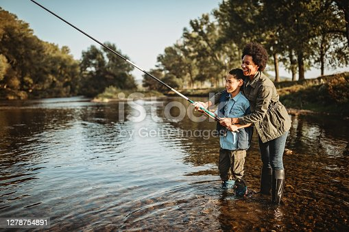 istock Mother teaching her son how to catch a fish 1278754891