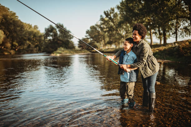 Mother teaching her son how to catch a fish stock photo