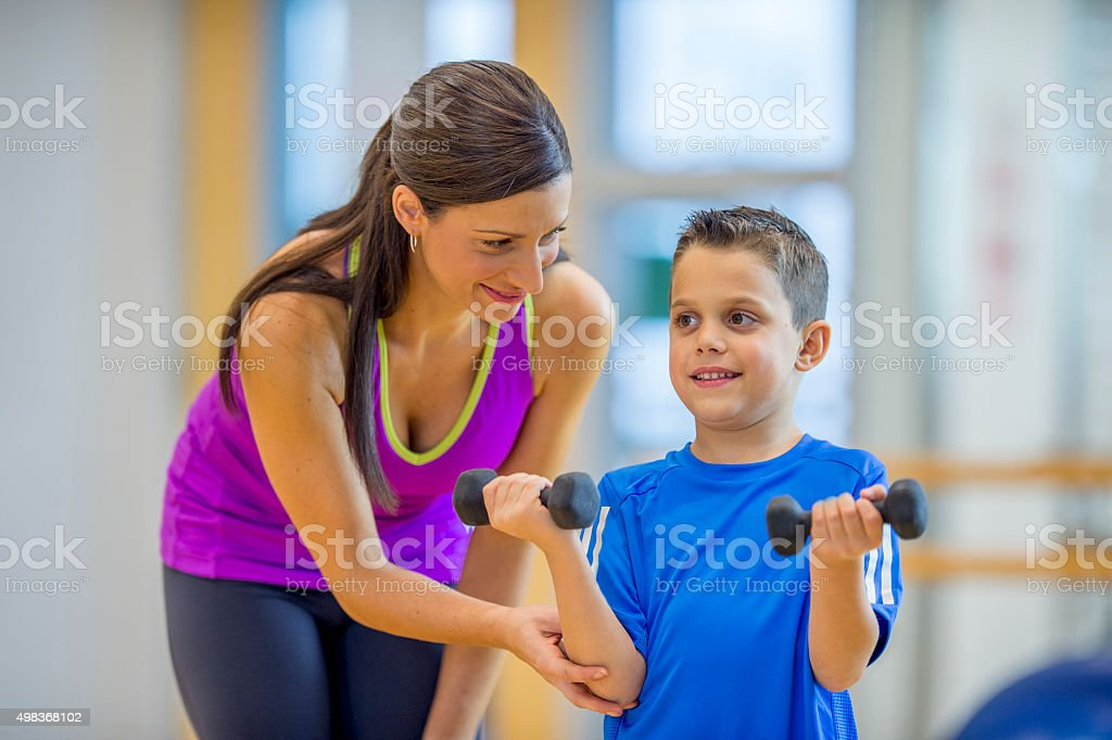 Mother Teaching Her Son How to Lift Weights stock photo