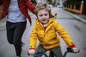 istock Mother teaching her son to ride a bicycle 1220209883