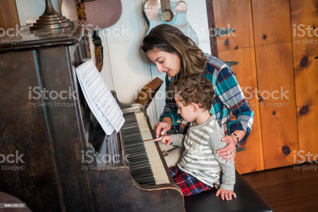 Mother teaching son to play piano stock photo