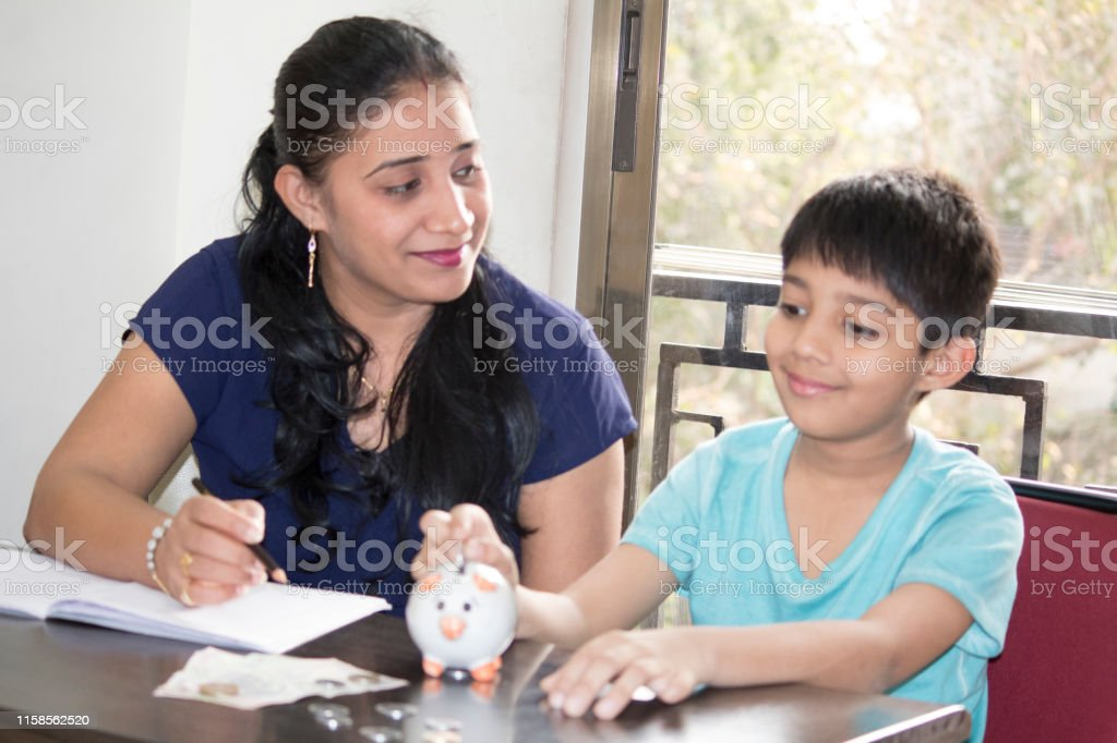 Mother with her son inserting coin into piggy, savings for education...