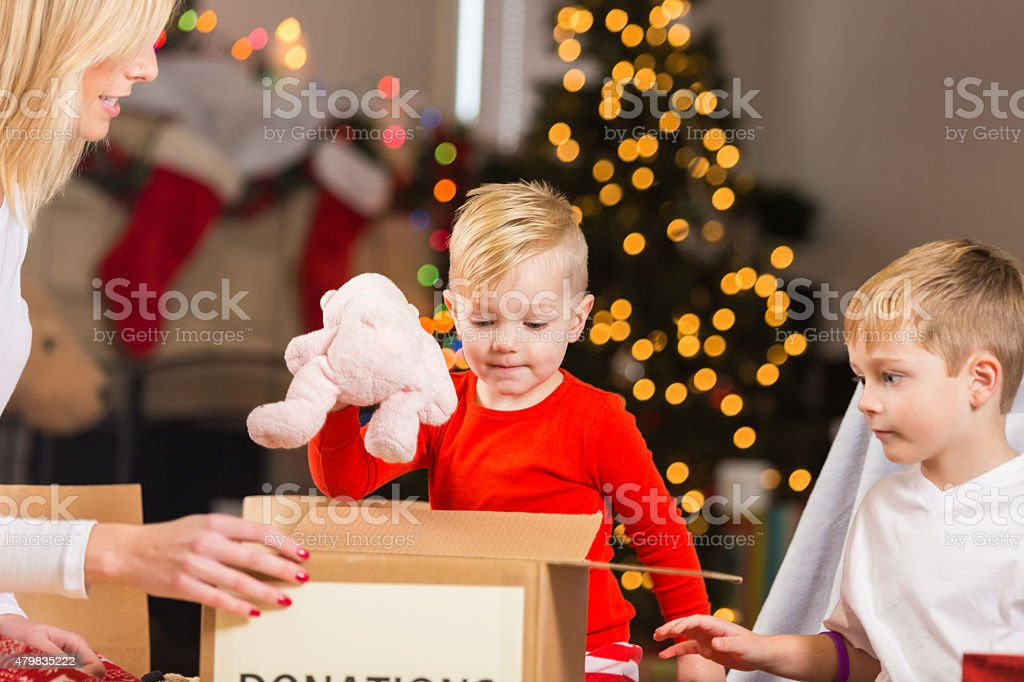 Mother Teaching Young Sons To Give By Donating Christmas Gifts Stock Photo Download Image Now Istock