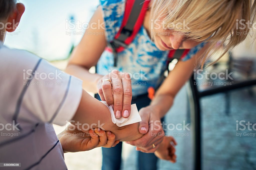 Mother tending to her son's wounded arm stock photo