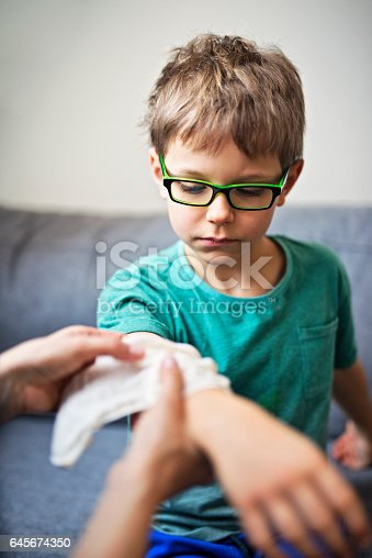 istock Mother tending to her son's wounded arm 645674350