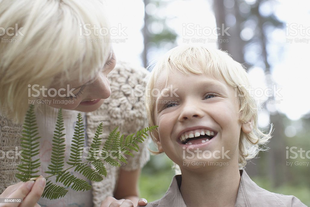 Mother tickling son with fern leaf royalty-free stock photo