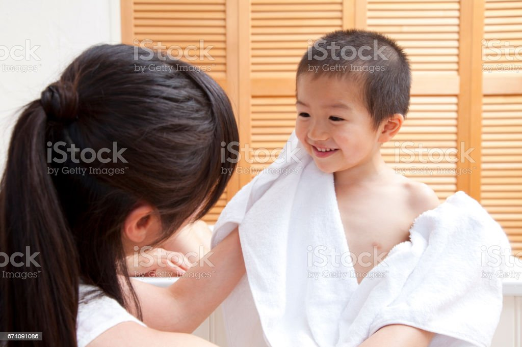 Mother to son's body wipe with a towel royalty-free stock photo