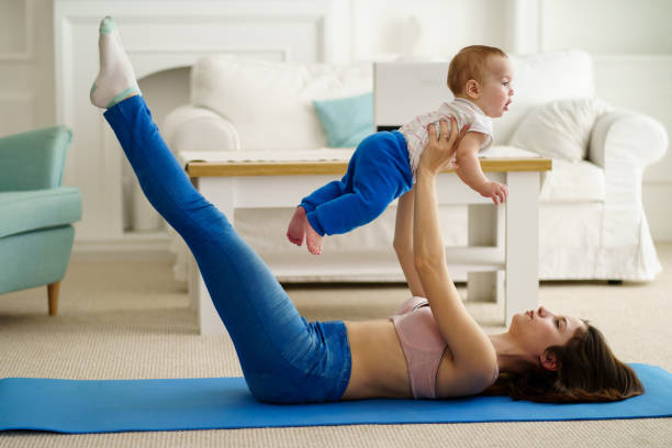 mother training at home together with baby son young active mother training at home, doing abs exercise together with her little cute toddler son. fitness, motherhood, parent, sport, healthy lifestyle exercises with baby stock pictures, royalty-free photos & images