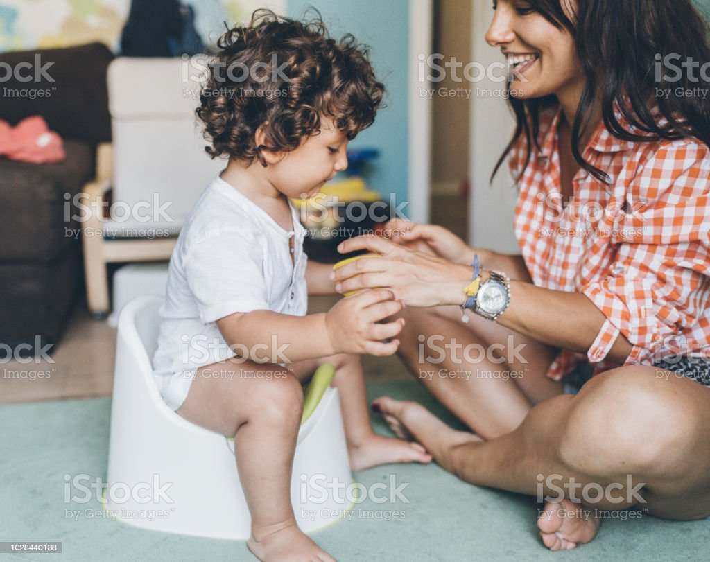 Mother Training Her Son to Use Potty stock photo