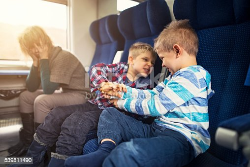istock Mother travelling on train with naughty kids 539811490