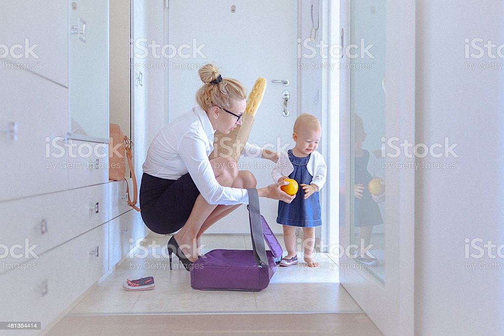 Mother trying to cheer her baby by giving her orange stock photo