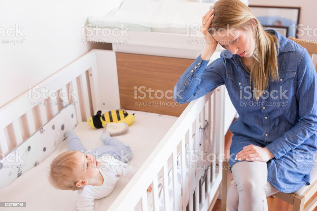 Mother trying to put her baby to sleep stock photo