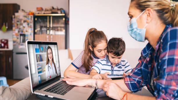 Mutter versucht, mit Arzt auf Laptop zu sprechen, während zwei Kinder zu beobachten – Foto