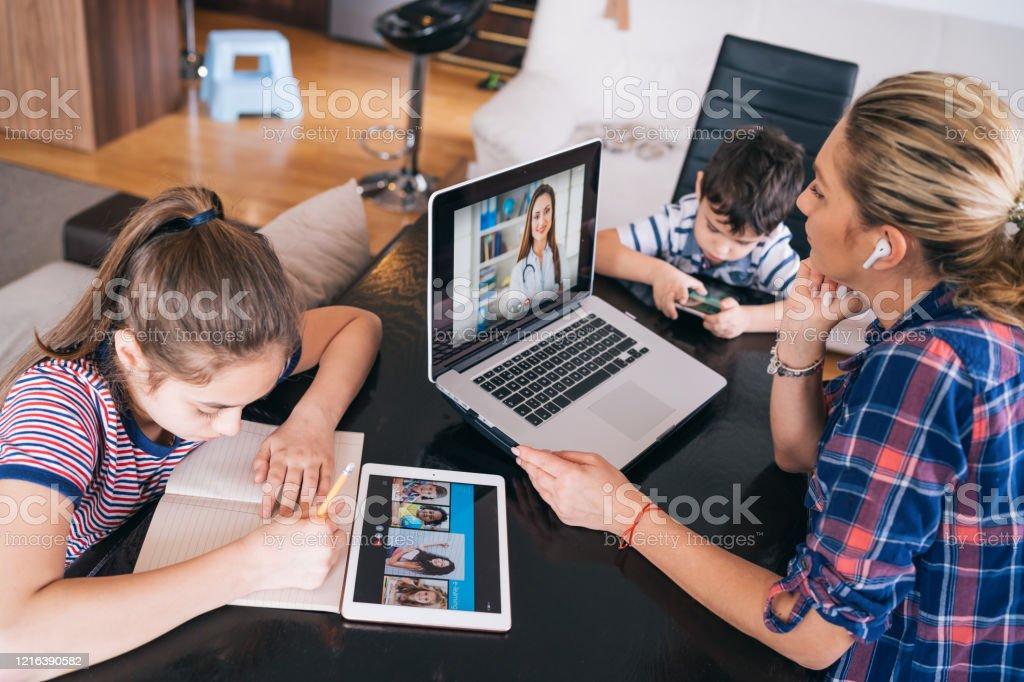 Mutter versucht, mit Arzt auf Laptop zu sprechen, während sie zwei Kinder zu Hause homeschooling und Fernunterricht bleiben - Lizenzfrei Abgeschiedenheit Stock-Foto