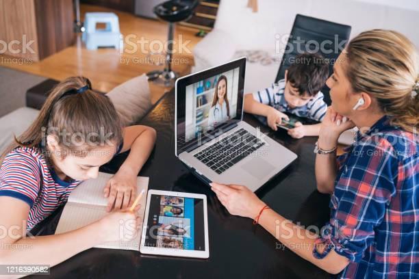 Mutter Versucht Mit Arzt Auf Laptop Zu Sprechen Während Sie Zwei Kinder Zu Hause Homeschooling Und Fernunterricht Bleiben Stockfoto und mehr Bilder von Abgeschiedenheit