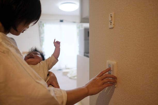 mother turning on the light with her baby in her arm - day in the life series stock pictures, royalty-free photos & images