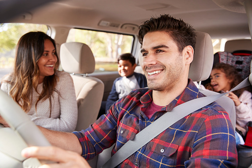 istock Mother turns around to her children on the back seat of car 1030960660