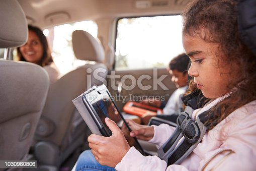 istock Mother turns around to kids using tablets in the back of car 1030960806