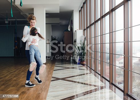 istock Mother twist her daughter in the gym 477252098