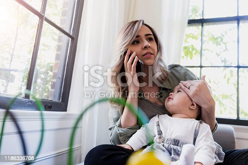 The mid adult mother uses her smart phone to call the doctor about the baby's fever.