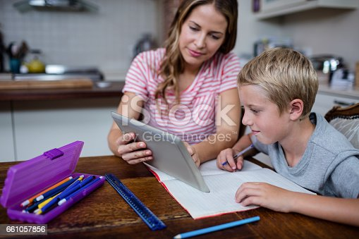 istock Mother using a digital tablet while helping son with his homework 661057856