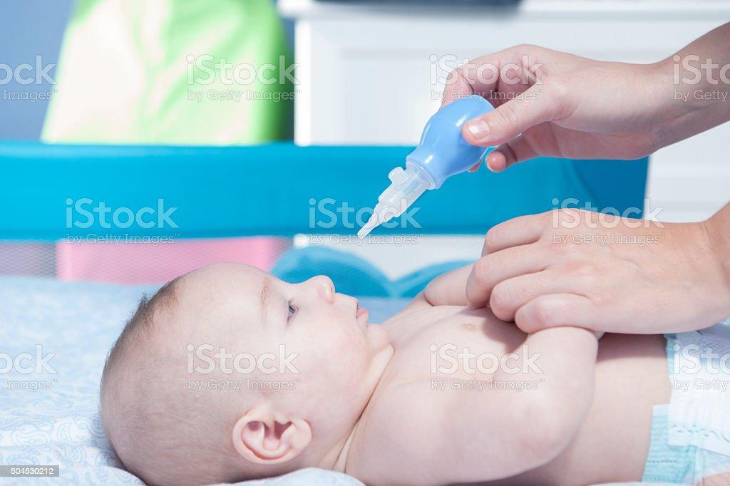 Mother using baby nasal aspirator stock photo