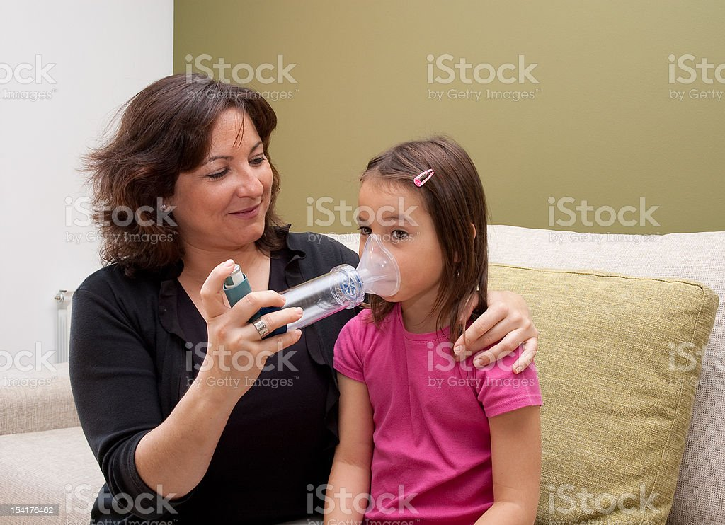 mother using inhaler stock photo